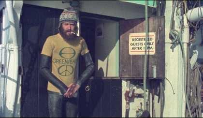 A man in a GreenPeace t-shirt and toque standing in the cold and smoking a cigarette.