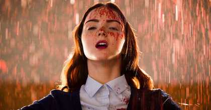 A young female student looking exultant with blood on her face and school uniform while blood rains down all around her.