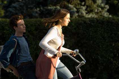 A teenage girl pedaling a bicycle with determination toward the setting sun while a teenage boy sits behind her.